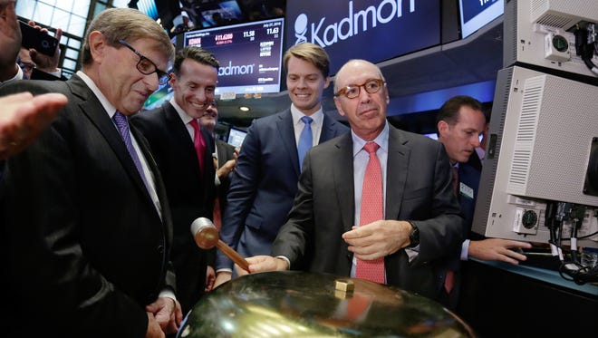 Kadmon Holdings President & CEO Harlan Waksal (R) rings a ceremonial bell to mark the beginning of trading of his company's IPO, on the floor of the New York Stock Exchange.