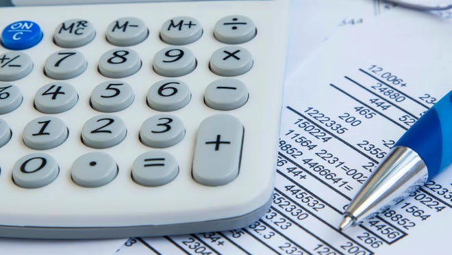 Stock image showing a calculator and other financial information.