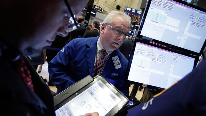 In this Monday, Sept. 26, 2016, file photo, trader James Dresch, center, works on the floor of the New York Stock Exchange. (AP Photo/Richard Drew, File)