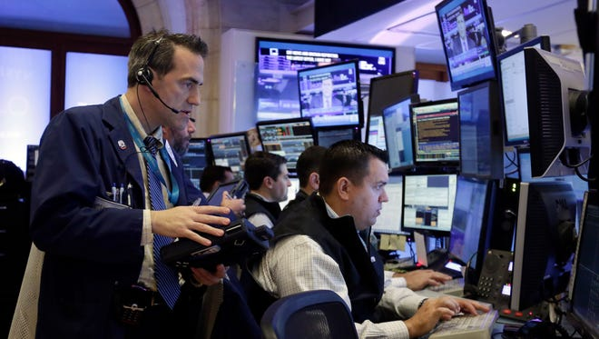Trader Gregory Rowe, left, works with colleagues in their booth on the floor of the New York Stock Exchange, Monday, Oct. 12, 2015. (AP Photo/Richard Drew)