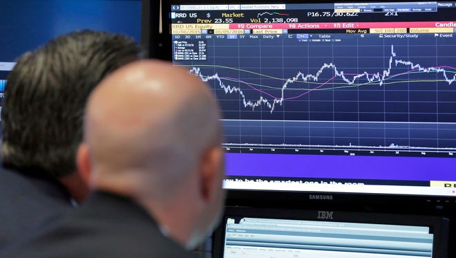 A pair of specialists study a screen at a post on the floor of the New York Stock Exchange Oct. 5.