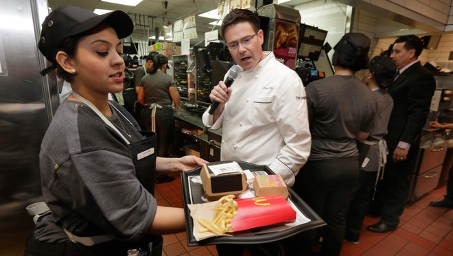McDonald's Executive Chef Dan Coudreaut checks an outgoing order in the kitchen at a McDonald's restaurant, during a presentation in New York's Tribeca neighborhood, Thursday. On Thursday, the company said it wants to makes its fast-food outlets feel more like restaurants, with plans to eventually expand table service across its U.S. locations.