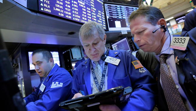 Traders Richard Newman (center) and Robert Charmak (right) work on the floor of the New York Stock Exchange. U.S. stocks are in the midst of a strong year-end rally.