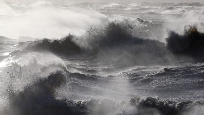 Large waves, produced by storm force winds, break on the shore.