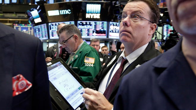In this Thursday, Oct. 27, 2016, file photo, trader Joseph Murray works on the floor of the New York Stock Exchange. After reaping big returns from stocks and bonds for years, investors need to prepare for weaker gains in 2017 and future years, strategists say. It's a result of simple math: Stocks no longer look cheap, and bond prices will likely be hurt by rising interest rates.