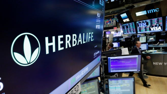FILE - In this May 6, 2016 file photo, the Herbalife logo appears above the post where it trades on the floor of the New York Stock Exchange.   The Federal Trade Commission is closing an investigation of Herbalife and the multinational, nutritional supplements company will to pay $200 million to settlement allegations that it deceived consumers.  The company said in a written statement on Friday, July 15,  that the FTC settlement doesn't change its business model as a direct selling company. (AP Photo/Richard Drew)