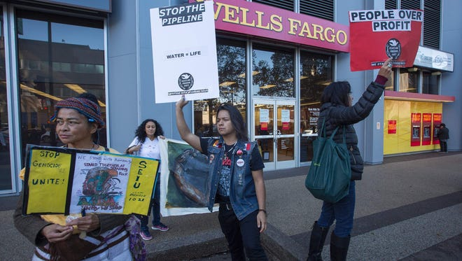 Supporters of the Standing Rock Water Protectors call on banks to divest from the Dakota Access Pipeline, under construction near the Standing Rock Sioux reservation in North Dakota, outside a Wells Fargo Bank branch on December 16, 2016 in Los Angeles, California.