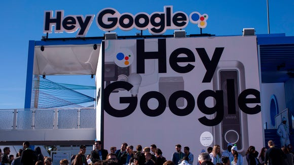 People walk past the Google exhibit during CES 2018