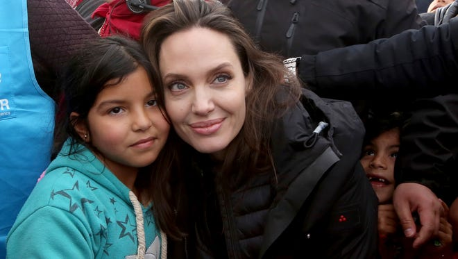 The U.N. refugee agency's special envoy, actress Angelina Jolie, poses with a Syrian child during her visit to the Zaatari Syrian Refugee Camp, in Mafraq, Jordan, on Jan. 28, 2018.