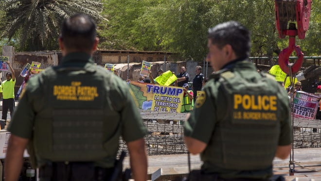 Border agents watch as protesters on the Mexico side of the border demonstrate against policies of President Trump while Homeland Security Secretary Kirstjen Nielsen tours a border fence construction site on April 18, 2018 in Calexico, Calif.