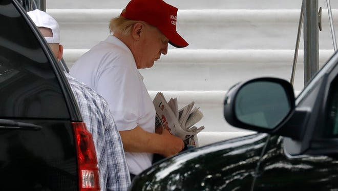 President Donald Trump holds newspapers as he returns to the White House in Washington from Trump National Golf Club in Washington last month.