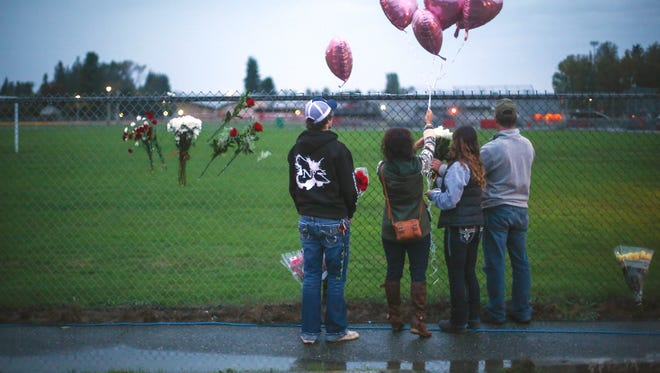 A memorial grows Saturday, Oct. 25, 2014 at the entrance to Marysville-Pilchuck High School the day after a shooting in the school cafeteria left two dead and four wounded. Authorities on Monday released the names and causes of death of one of the victims and the gunman killed.