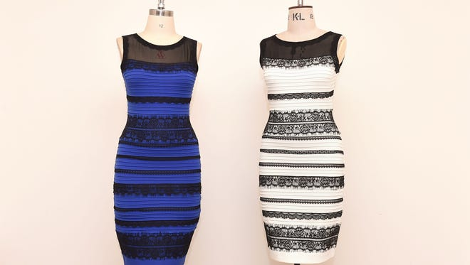 The two-tone dress, left,  alongside an ivory and black version, made by Roman Originals, that has sparked a global debate on Twitter over what color it is on display in Birmingham, England Friday, Feb. 27, 2015.