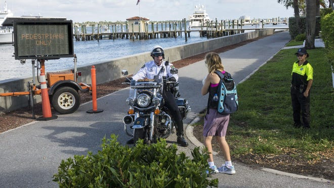 A Palm Beach police officer answers questions about the new rules for Lake Trail, and what is and is not allowed in the town in general, from a woman on March 29.