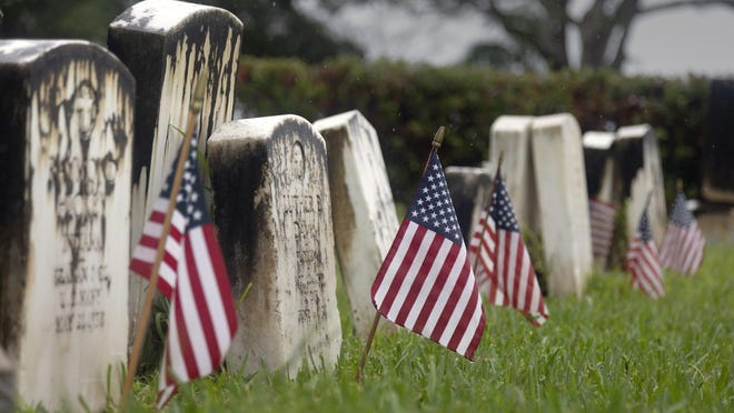 Flags mark the graves of veterans at Woodlawn Cemetery in West Palm Beach on Sunday as the nation moved toward 100,000 deaths from COVID-19.