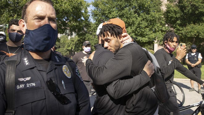 University of Texas football player Caden Sterns, right, hugs head coach Tom Herman at the end of a team march to the Capitol on June 4 to protest the killing of George Floyd. After many athletes and other students spoke out, UT is changing its diversity and recruitment efforts.