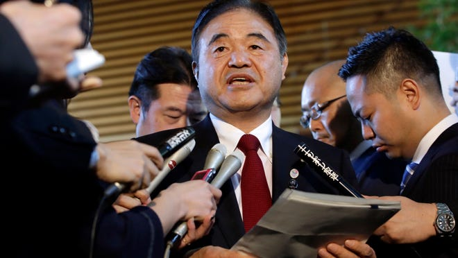 In this Dec 22, 2015, file photo, Toshiaki Endo, center, minister in charge of the 2020 Tokyo Olympics, speaks with media after a meeting of Cabinet ministers including Japan's Prime Minister Shinzo Abe, at Abe's official residence in Tokyo. Former Olympic minister Endo said at a meeting of the ruling Liberal Democratic Party on Friday, June 5, 2020, that a decision of whether to hold the Games should be made around March, which is a crucial time to finalize participating athletes, NHK said.