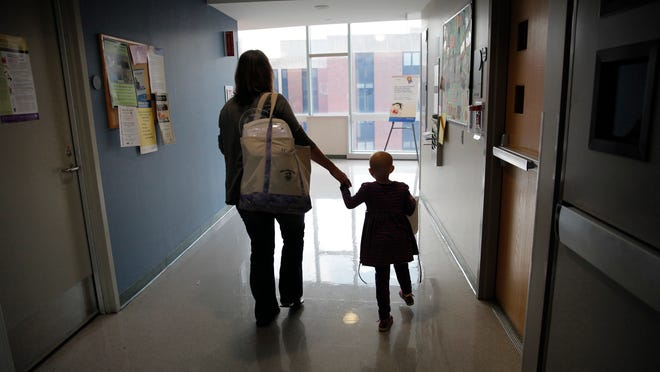 Liz Conrow, left, holds the hand of her daughter, Amanda Conrow, as they leave Golisano Children's Hospital after one of Amanda's many regular treatments for brain cancer.