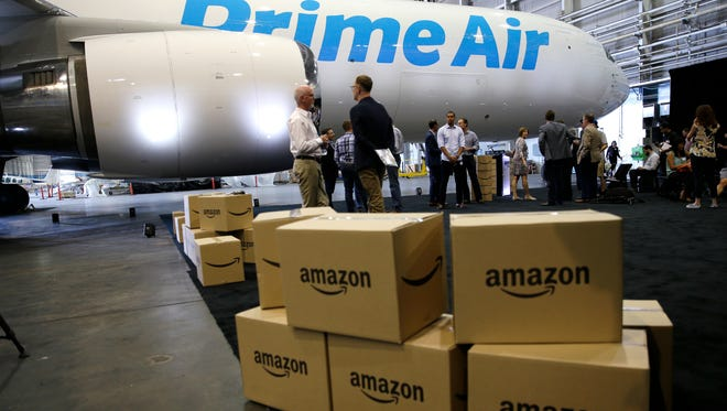"FILE - In this Aug. 4, 2016 file photo, Amazon.com boxes are shown stacked near a Boeing 767 Amazon ""Prime Air"" cargo plane on display in a Boeing hangar in Seattle."