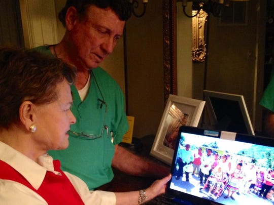 Dr. Tom Robinson and his wife, Daphne, look at a digital picture of patients who dressed in their finery before getting treatment from him during one of his recent mission trips to Mexico.