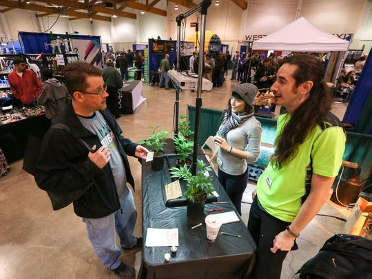 David Allen, left, speaks with Jason Overhaul, right, and Monique White with Sweet Leaf Starts talk about the plants they have on display during The Hemp and Cannabis Fair, Sunday, November 15, 2015, at the Oregon State Fairgrounds in Salem, Ore.