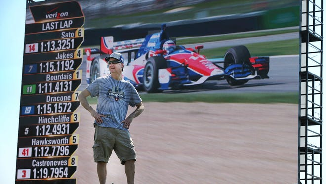IndyCar fan Chris Hagan  watches the cars round turns two and three from a viewing mound during practice for the Angie's List Grand Prix of Indianapolis Thursday, May 7, afternoon at the Indianapolis Motor Speedway.