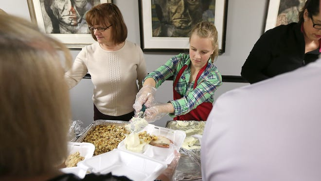 Lauren Stevens, of Grimes, places a scoop of mashed potatoes into a container on Nov. 28, 2013 at Chuck's Restaurant in Des Moines as volunteers packaged up hundreds of meals for Thanksgiving dinner to be delivered to area families.