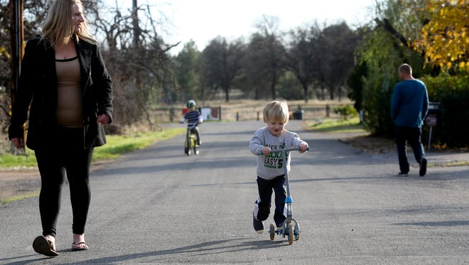 Heather McSweeney-Pope, left, and her boyfriend Jeramie Brooks, right, watch as Brook's kids Wiatt, 2, foreground, and Samual, 7, background ride bikes Monday at their home in Redding. McSweeney-Pope recently had power restored to her home after it was shutoff earlier in the year because she fell behind on her bills.