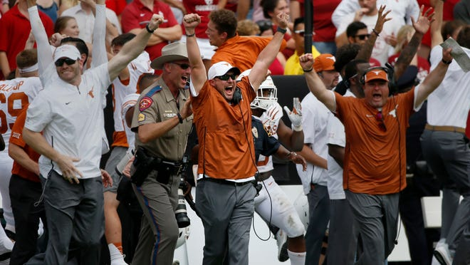 FILE- In this Oct. 6, 2018, file photo, Texas coach Tom Herman, center, celebrates with other staff members after the final play of an NCAA college football game against Oklahoma in Dallas. After years of being a late-season afterthought, Herman wanted the Longhorns to be competing for a Big 12 title in November. Texas is right where he wanted, with a key matchup against West Virginia to see just how long they stay there.  (AP Photo/Roger Steinman, File)