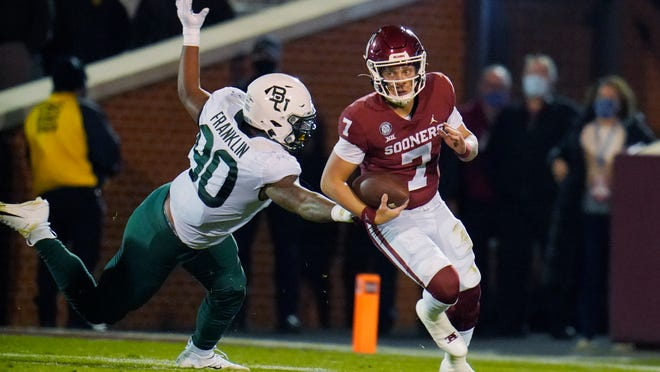 Oklahoma quarterback Spencer Rattler is pursued by Baylor linebacker Hakeem Vance in the first half of their game in Norman, Okla.