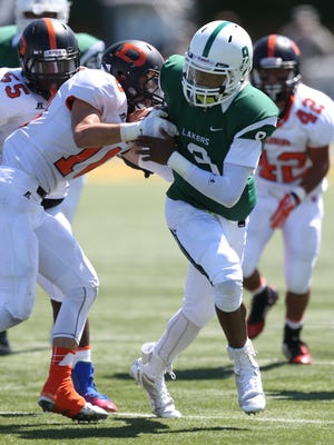 West Bloomfield's Trishton Jackson is tackled by Dearborn's Ahmed Hazime on Aug. 28, 2014.