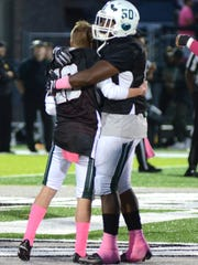 Nick O'Shea, left, gets a hug from his teammate Blake Barnes before West Bloomfield's game against Birmingham Groves in Friday, Oct. 20, 2017.  O'Shea's father, Dan, died of a heart attack on Oct. 10.