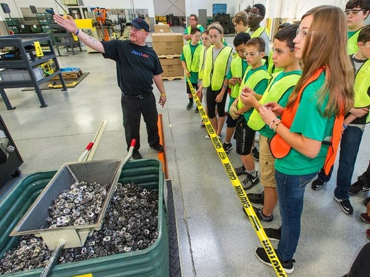 Jeff Pinke, assembly cell technician for Alpha USA, shows students the manufacturing process.