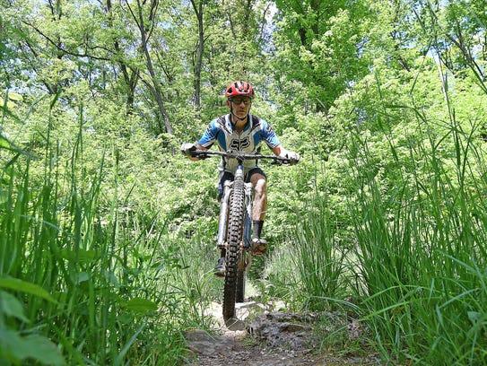 Michael Jarosick takes his mountain bike over rocks