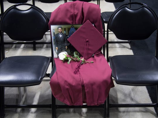 A seat is reserved for Zaevion Dobson's cap and gown at Fulton High's graduation at Thompson-Boling Arena on Thursday, May 17, 2018.
