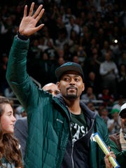 Former Michigan State player Morris Peterson waves as he is introduced with Michigan State's 2000 national championship team during halftime of the Michigan State-Florida NCAA college basketball game, Saturday, Dec. 12, 2015, in East Lansing, Mich.