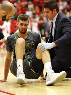 Vermont's Ethan O'Day is assisted by trainers during the Catamounts' 80-74 loss to Stony Brook in the America East championship game at Stony Brook, N.Y., March 12.