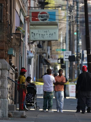 Bystanders watch as Cincinnati Police investigate the scene of a shooting on Vine Street north of Liberty Saturday afternoon.