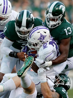 Michigan State's Montae Nicholson, left, Vayante Copeland (13) and Chris Frey, bottom right, tackle Furman's Darius Morehead, center, during the second quarter of an NCAA college football game, Friday, Sept. 2, 2016, in East Lansing.