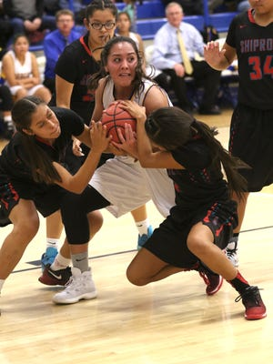 Bloomfield's Destiny Walther, center, battles Shiprock defenders for possession on Tuesday at Bobcat Gym in Bloomfield.