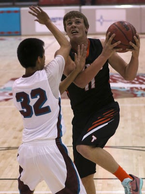 Aztec's Cody Smith goes up for a shot against Shiprock's Aaron Gould on Friday night at the Chieftain Pit.