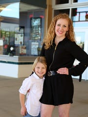Maddox Robinson, with his mother Kelley, poses in front of Regal Stadium Hollywood 20 in Greenville.