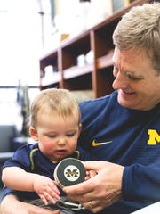 Michigan hockey coach Mel Pearson plays with his grandson, Finnley, in his office at Yost Ice Arena in Ann Arbor.