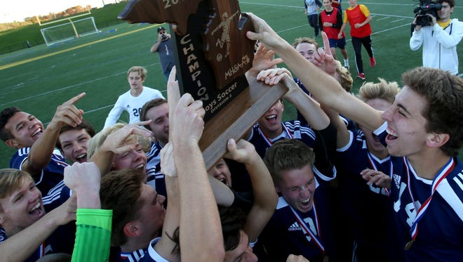 Mattawan celebrates with their championship trophy after defeating Dearborn Divine Child at the MHSAA Division 2 boys soccer finals at Stoney Creek High School in Rochester Hills, Michigan on Saturday, November 5, 2016.Mattawan won the game in a shootout.Eric Seals/Detroit Free Press