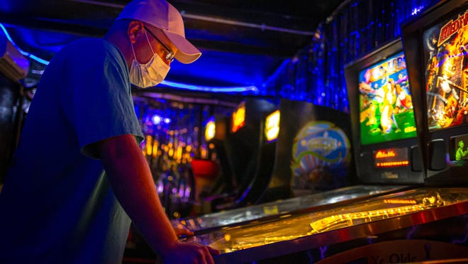 "Alex Rickman plans the ""Medieval Madness"" pinball machine in the new Dumb Arcade at Dumb Records on East Monroe Street, Saturday, July 18, 2020, in Springfield, Ill. The Dumb Arcade is a new addition to Dumb Records that allows visitors to play classic arcade games and pinball machines for a flat fee of $5 or with $10 of any purchase in the store. The machines are cleaned often and only four people are allowed at once as well as masks being required because of the COVID-19 pandemic."