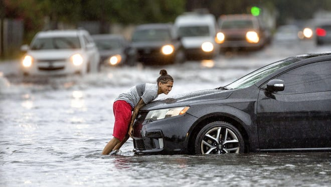 Anayeli Lugo pushes the car of her friend, Yanes Caraballo on Haverhill Road  after streets flooded in Greenacres, Florida on August 5, 2019.