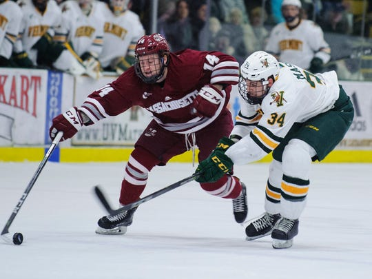 Vermont defenseman Jake Massie  (34) and UMass's Austin Plevy (14) battle for the puck during the men's hockey game between the UMass Minutemen and the Vermont Catamounts at Gutterson Fieldhouse on Friday night January 12, 2018 in Burlington.
