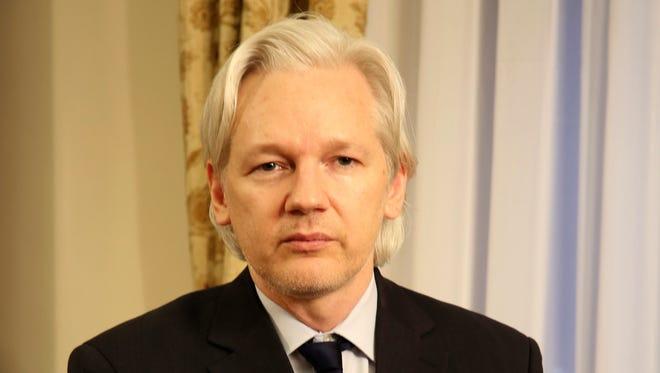 WikiLeaks founder Julian Assange sits inside the Ecuadorian Embassy in London on July 30, 2013.