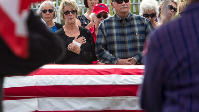 """Diana Young Long (center) stands with her husband, Greg Long, as her father, Herbert """"Buddy"""" Young Jr., is laid to rest in Prescott. pay their respects during the burial service for Herbert V. Young Jr., a first lieutenant pilot in the U.S. Army Air Force during World War II, at the Prescott National Cemetery, on Wednesday, Oct. 15, 2014. Young crashed in his B-24 bomber in New Guinea 70 years ago, but his remains were recently recovered from the jungle and returned to Prescott for a burial service with his daughter who never met him."""