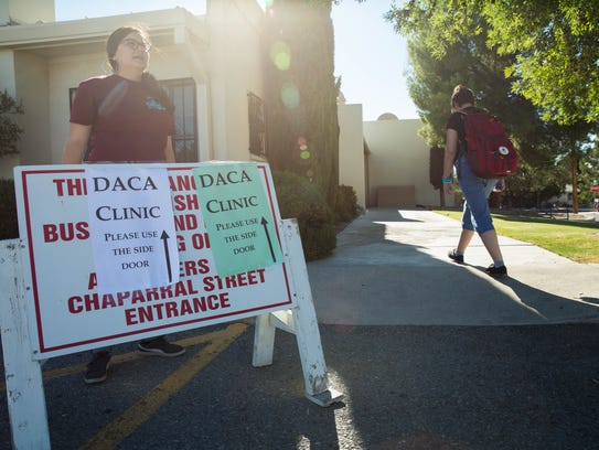 Amanda Orta, left, places a sign for the DACA clinic